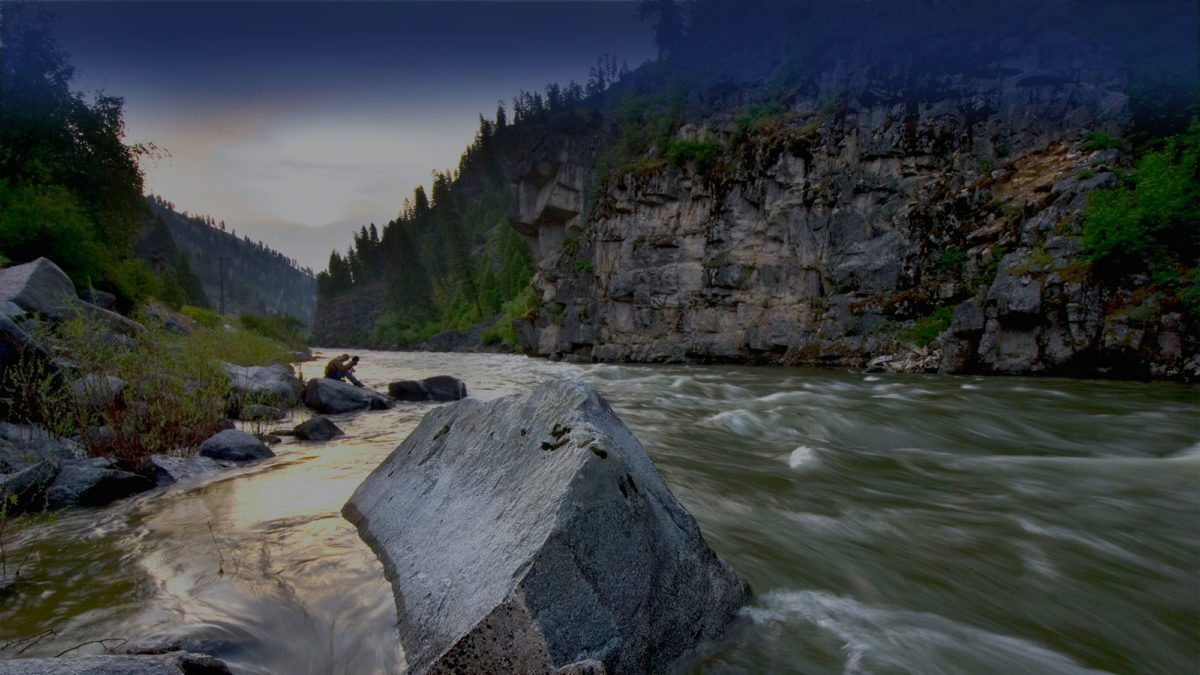 Sunrise reflecting off the fast-moving Payette River around a large Rock in the middle of the flow with a photographer in the distant background